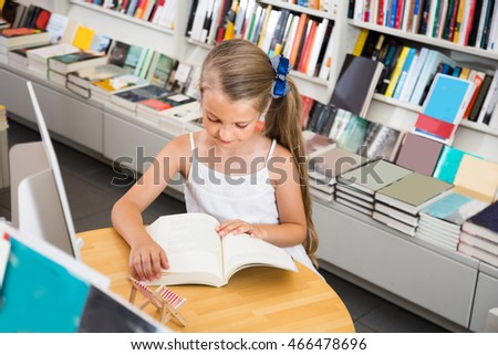 little smart girl reading a book in the school library