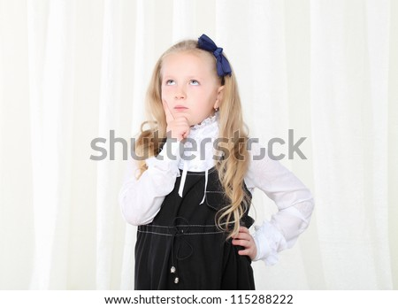 Little smart girl seriously thinking with hand near chin