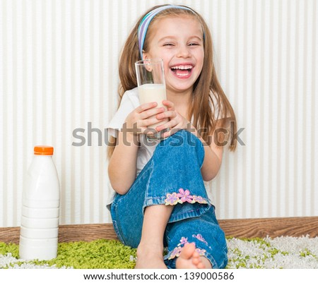 little smiley girl drink the milk  on the floor in her home