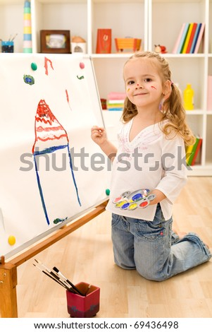 Little smiling artist girl painting her dream house on a large paper canvas - stock photo
