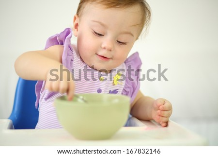 Little smiling baby sits at highchair and eats porridge on plate. Shallow depth of field. - stock photo