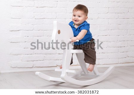 Little smiling baby sitting on a white horse, wooden rocking - stock photo