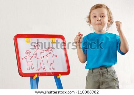 Little smiling boy drew a family on whiteboard - stock photo