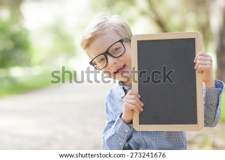 little smiling boy in cute glasses holding empty chalkboard, back to school concept - stock photo