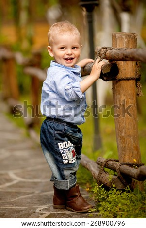little smiling boy in the blue shirt and jeans is standing near the fence in the nature - stock photo