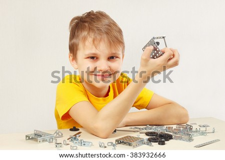Little smiling boy made something of the mechanical constructor - stock photo