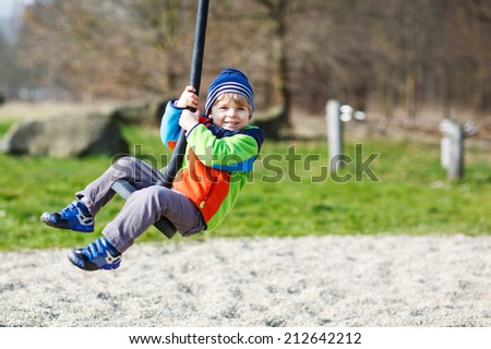 Little smiling boy of two years having fun on swing on cold day, outdoors. - stock photo