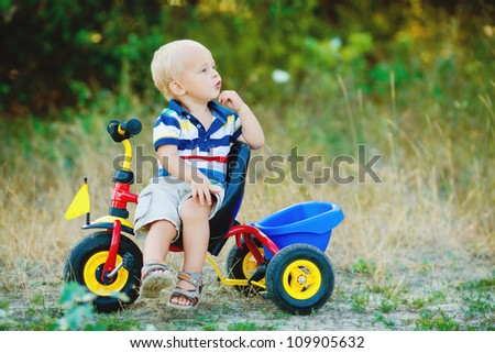 Little smiling boy on toy bicycle - stock photo