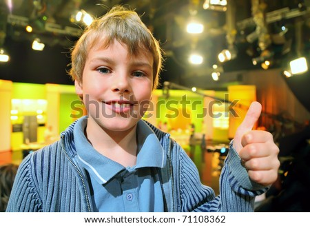 "Little smiling boy stands in auditorium and shows ""ok"" against the background of television broadcast - stock photo"