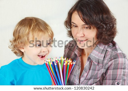 Little smiling boy with his mother with color pencils on a white background - stock photo