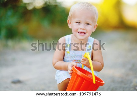 Little smiling boy with toy bucket outdoors - stock photo