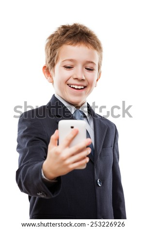 Little smiling child boy in business suit hand holding mobile phone or smartphone making selfie portrait photo white isolated