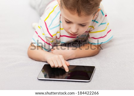 Little smiling child boy playing games or surfing internet on digital tablet computer - stock photo