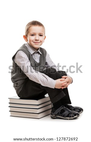 Little smiling child boy sitting on education reading books stack - stock photo