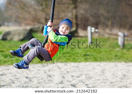 Little smiling child of two years having fun on swing on cold day, outdoors. - stock photo