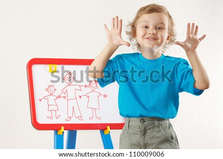 Little smiling cute boy shows his family painted on a whiteboard - stock photo