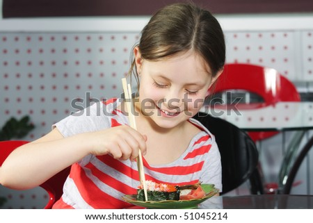 Little smiling girl eating sushi with wooden sticks - stock photo