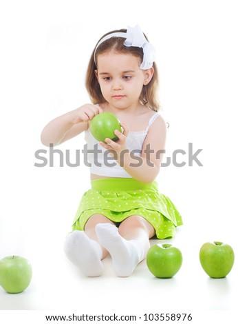 Little smiling girl holding green apples on white background - stock photo
