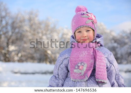 Little smiling girl in pink scarf and hat stands near trees in snow at winter day.