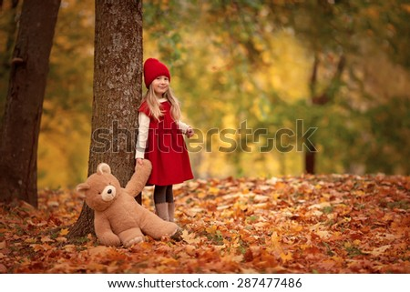 little smiling girl in red hat and red dress standing in the autumn park with teddy bear