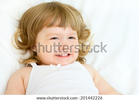 Little smiling girl on a bed - stock photo