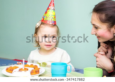 Little smiling girl sitting at the table in her birthday with mother - stock photo