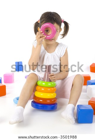 Little smiling girl sitting on the floor and playing with colored rings. Whole body, white background - stock photo