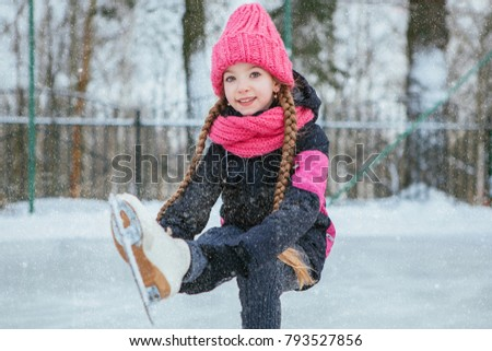 Little smiling girl skating on ice in pink wear. Outdoor