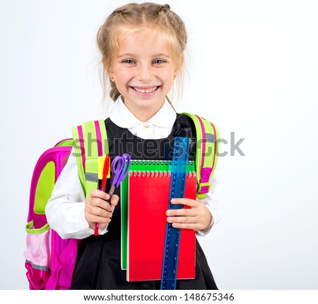 little smiling girl with a stationery on a white background - stock photo