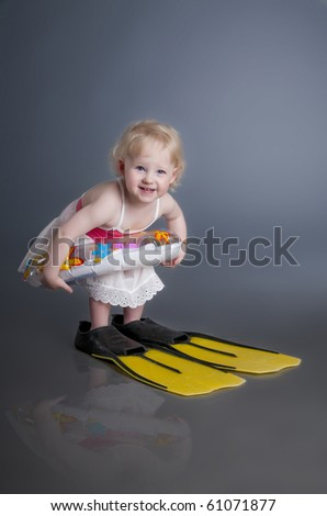 Little smiling girl with buoy and fins - stock photo