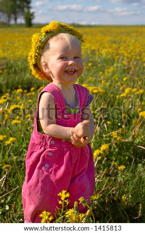 little smiling girl with dandelion diadem on a beautiful meadow