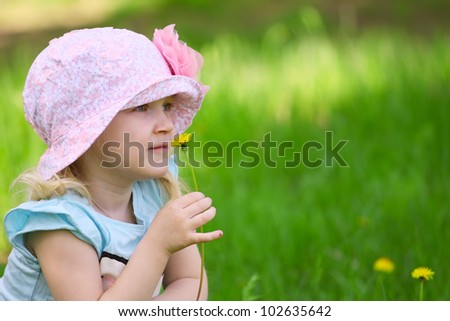 little smiling girl with dandelion on a grass in a park - stock photo
