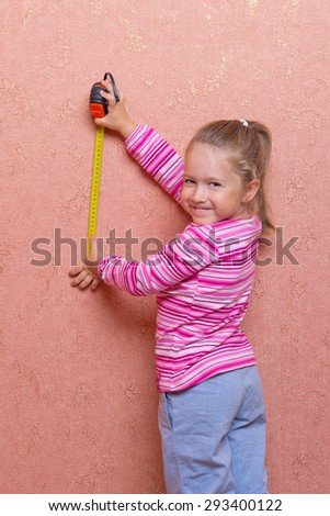 Little smiling girl with measurement tape - stock photo