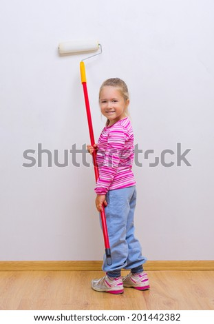 Little smiling girl with painting roller