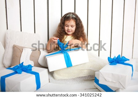 Little smiling toddler girl open gifts. Christmas, New Year, holiday concept - stock photo