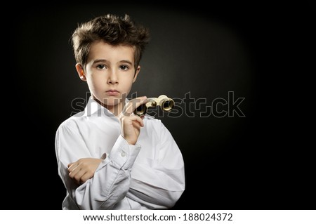 Little snobbish boy with theater binoculars in low key - stock photo