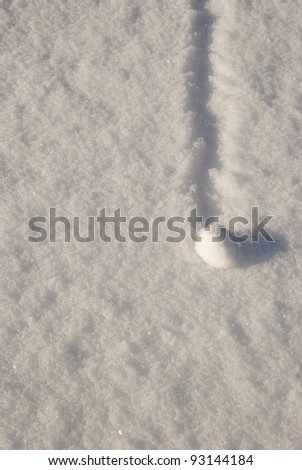 Little snowball path written on melting snow. - stock photo