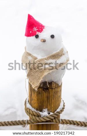 little snowman on wooden pole - stock photo