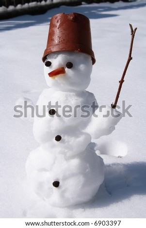 little snowman standing in the snow - stock photo