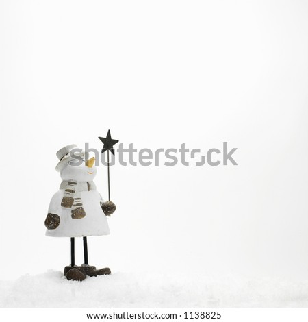 little snowman standing in the snow (copy space) - stock photo