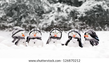 Little snowmen in a group carol singing in the snow - stock photo