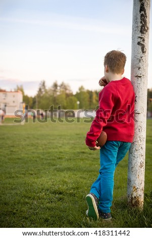 Little soccer player standing in the goalposts defending the the line and ready to throw a football. Cute kid boy standing as goalkeeper on a sports field on a sunny day Sport activities for children  - stock photo