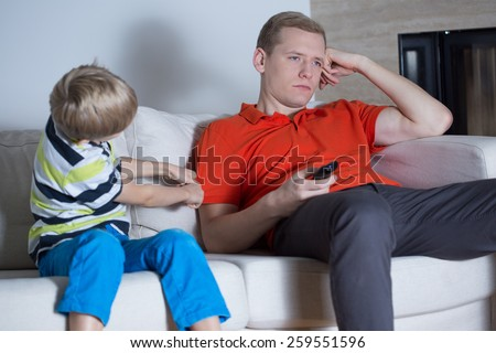 Little son encouraging his tired father for fun - stock photo