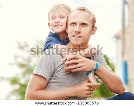 Little son hugs his father on neck - stock photo