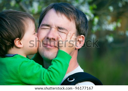 Little son kissing his father outdoors in spring park - stock photo