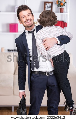 Little son meets his businessman father from work. - stock photo