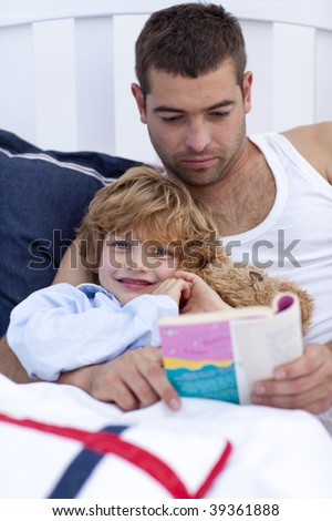 Little son reading with his father a book in bed - stock photo