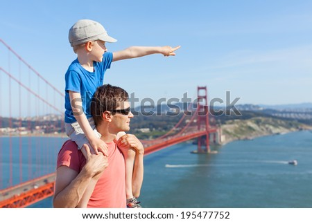 little son sitting at his father shoulders and enjoying together the view of golden gate bridge in san francisco, california - stock photo