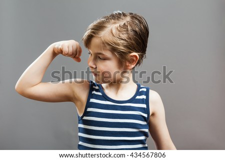 Little Sportive Tough Boy in striped  muscle shirt, looking at his muscles - stock photo