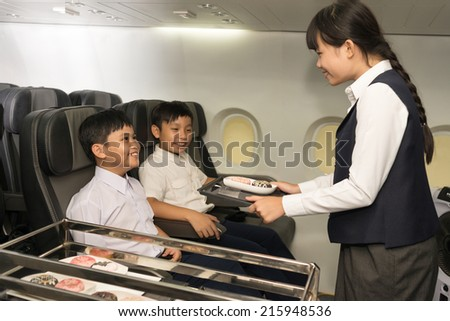 Little stewardess serving food to the passengers - stock photo
